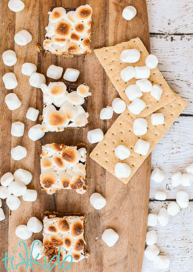 No bake s'mores bar squares on a wooden cutting board surrounded by marshmallows and graham crackers.