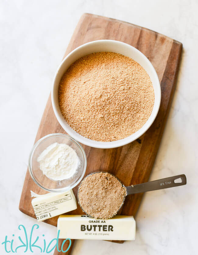 Graham cracker crust ingredients on a wooden cutting board.