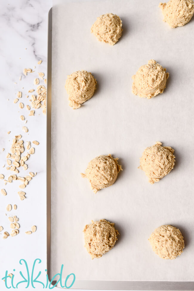Oatmeal cookie dough scooped on a parchment lined cookie sheet to make chewy oatmeal cookies.