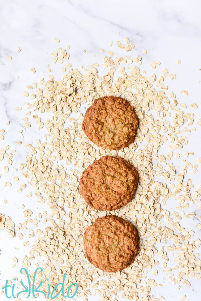 Three oatmeal cookies surrounded by uncooked oats.