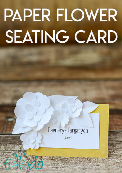 DIY Wedding seating card decorated with miniature paper flowers.