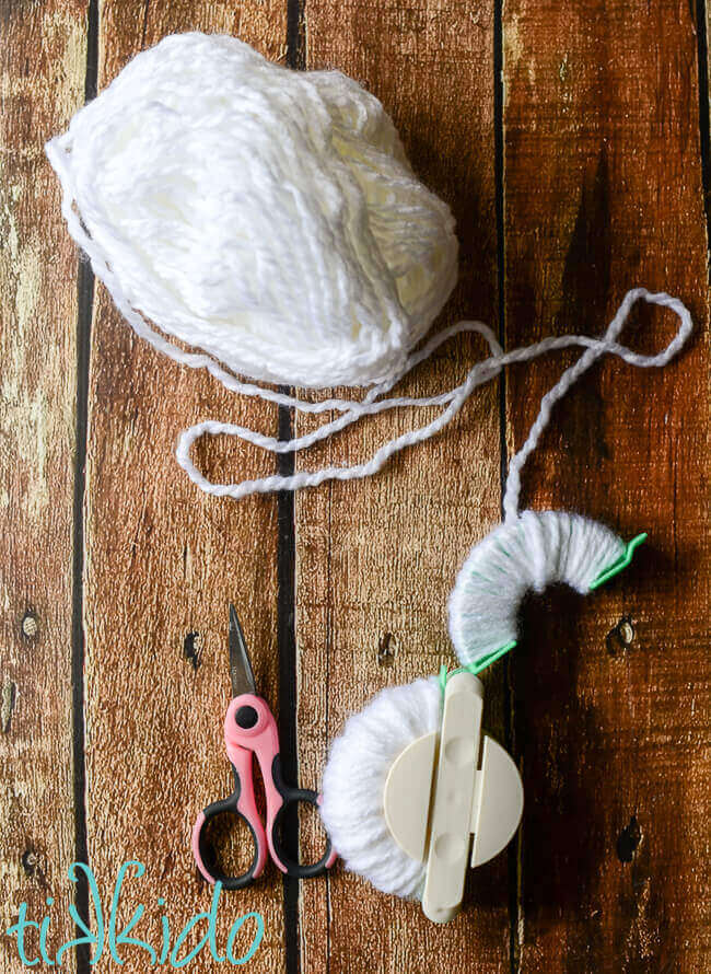 White yarn being wound around a pom pom maker tool to make snowball pom poms for a DIY Snowball Fight toy