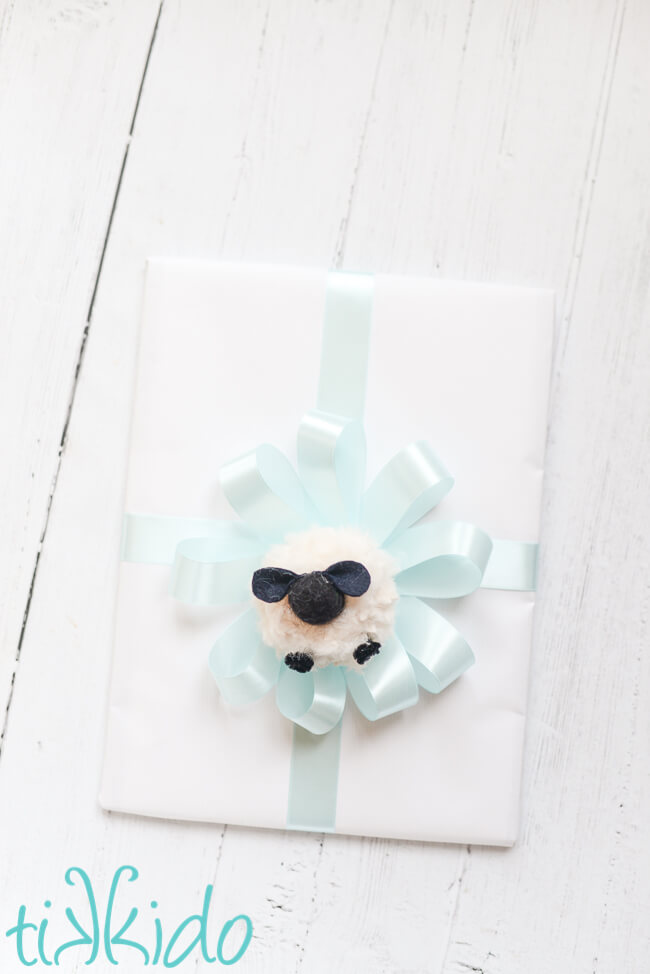 Pom Pom Sheep in the center of a bow on a baby shower gift.