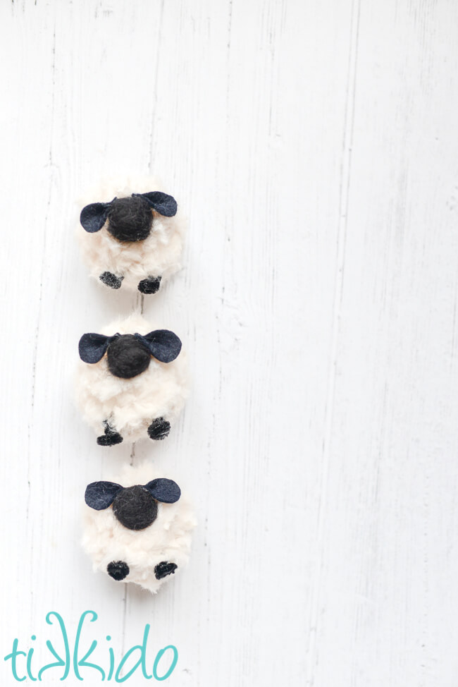 Three Pom Pom Sheep lined up vertically in a row on a white wooden surface.