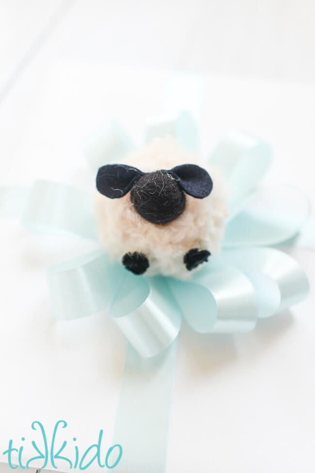 Pom Pom Sheep used as a gift topper for a baby shower gift.