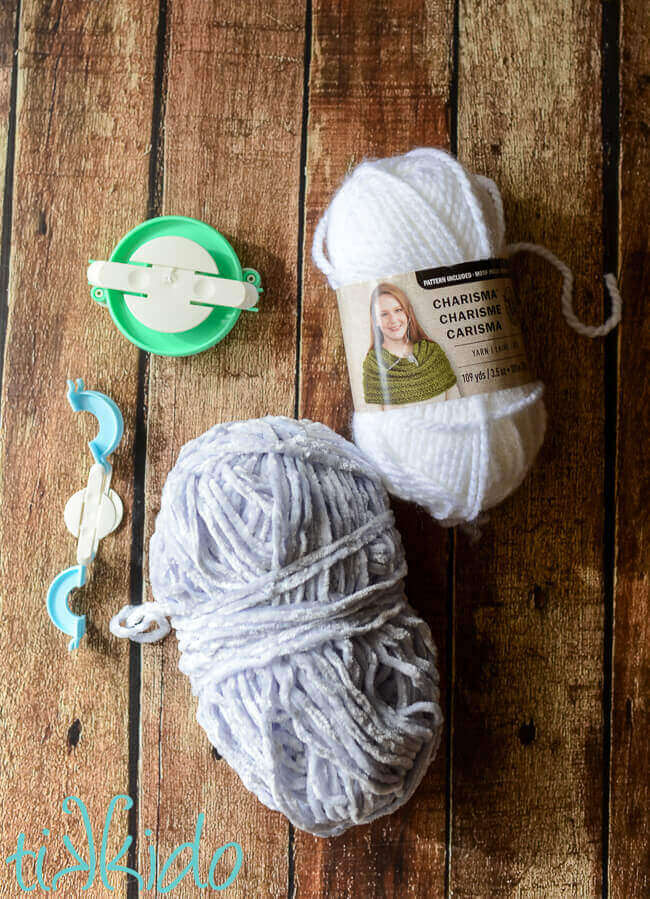 White and pale grey yarn next to two pom pom maker tools on a wooden backdrop.