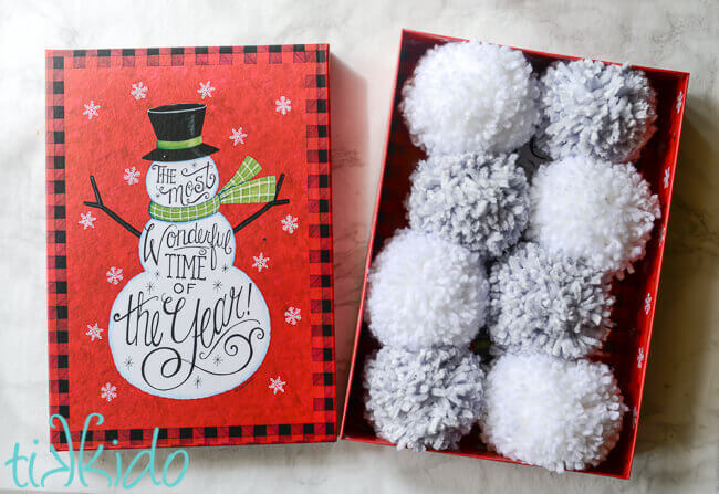 Yarn pom poms in a snowman themed gift box for a DIY Pom Pom Snowball Fight Kit
