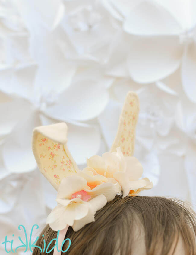Girl wearing Bunny ear headband made with cream colored felt, a peaches and cream colored calico fabric, and ivory silk flowers on a pink headband, in front of a white surface.