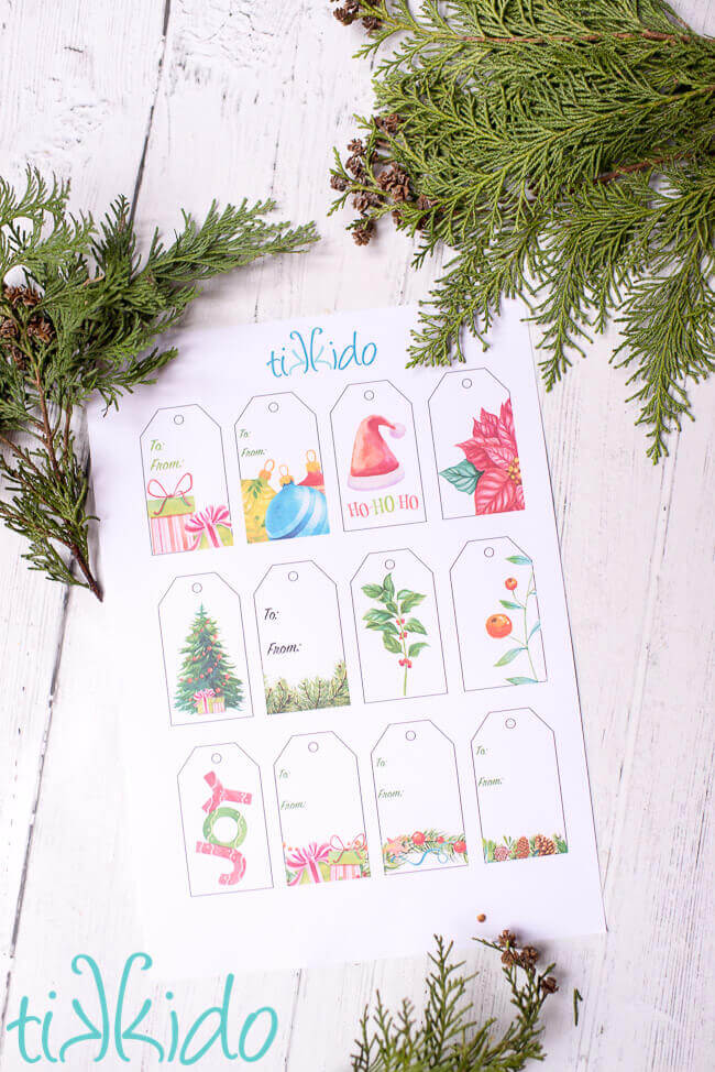 Sheet of Printable Christmas Gift Tags on a white wooden surface.