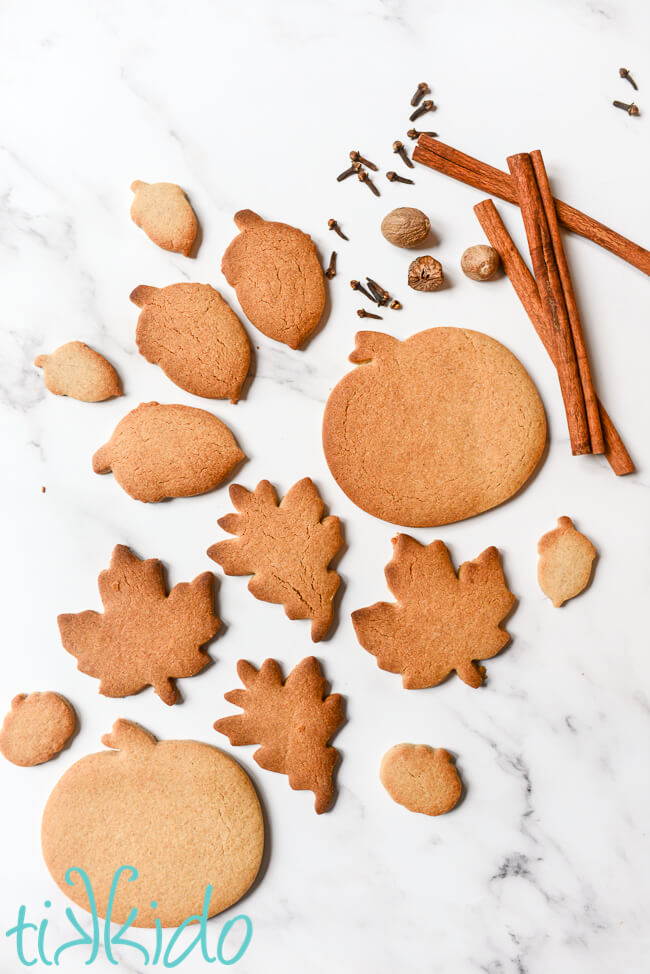Pumpkin Spice Sugar Cookies and whole pumpkin pie spices on a white marble surface.