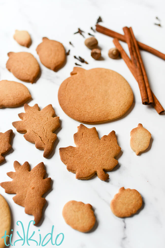 Pumpkin Spice cut out Sugar Cookies and whole spices on a white marble surface.