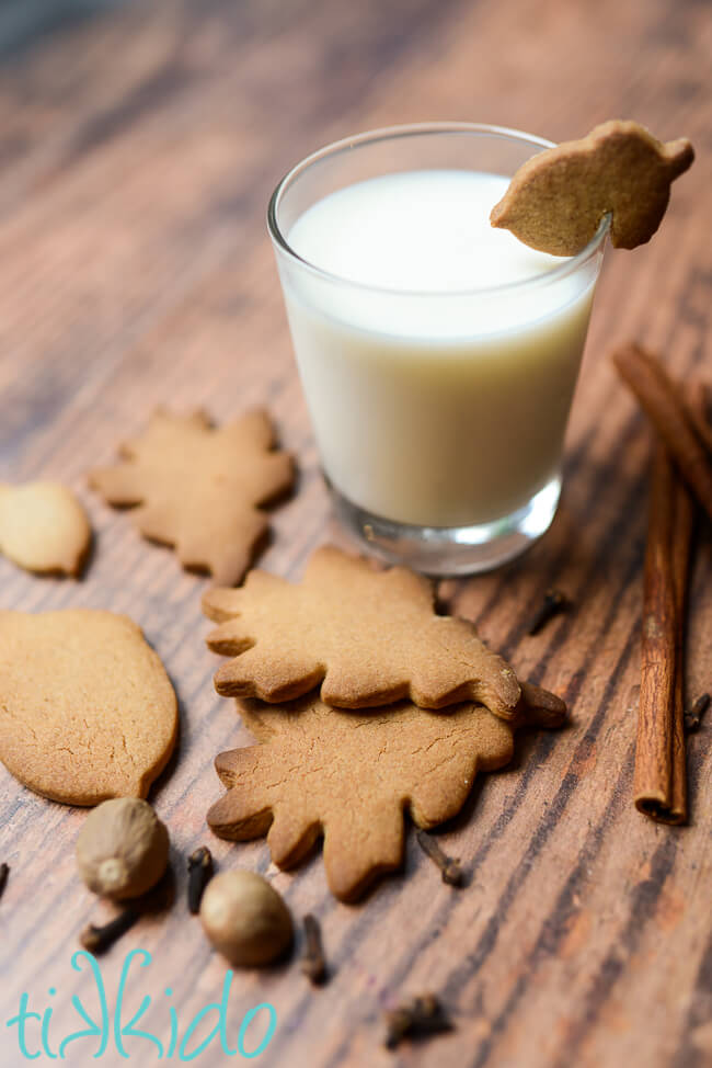 Pumpkin Spice Sugar Cookies and whole pumpkin pie spices on a table next to a glass of milk with a pumpkin spice cookie shaped like an acorn balancing on the rim.