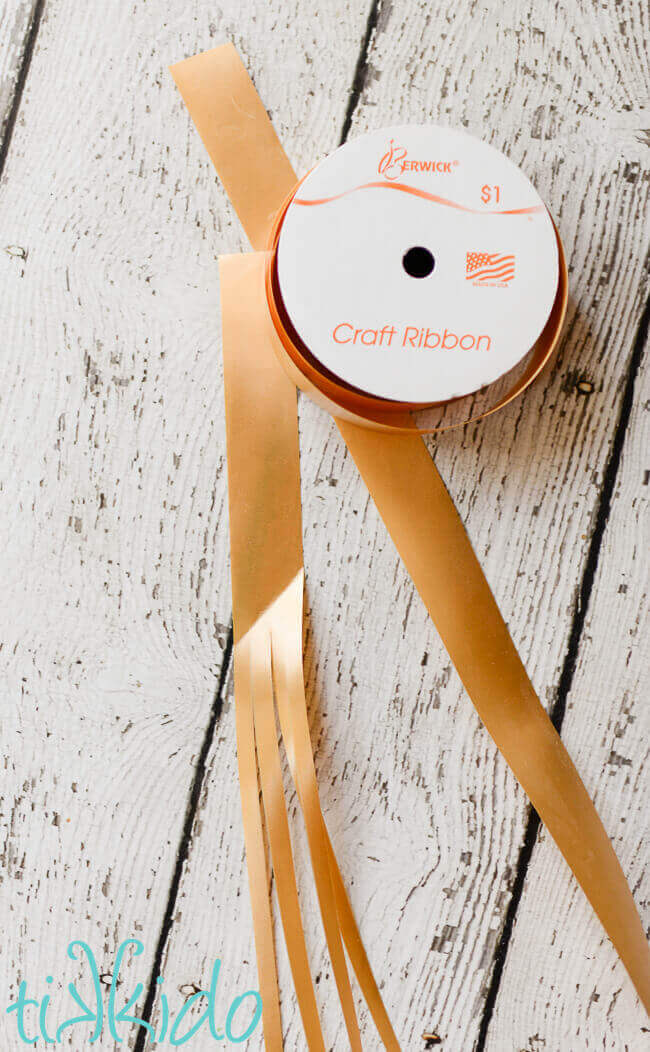 Golden craft ribbon spool and a piece of ribbon divided in four pieces on a white weathered wooden surface.