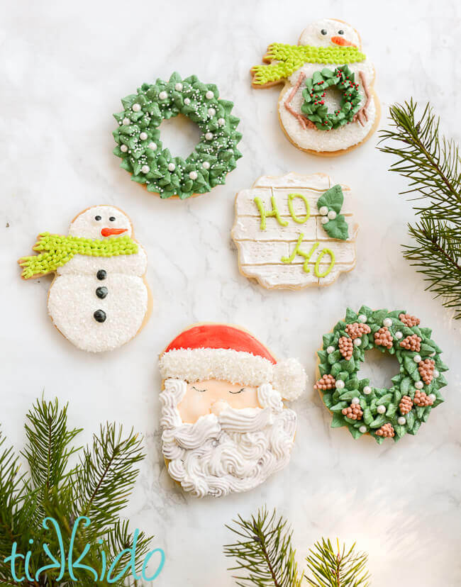 Santa, wreath, and snowman Christmas sugar cookies on a white marble surface.