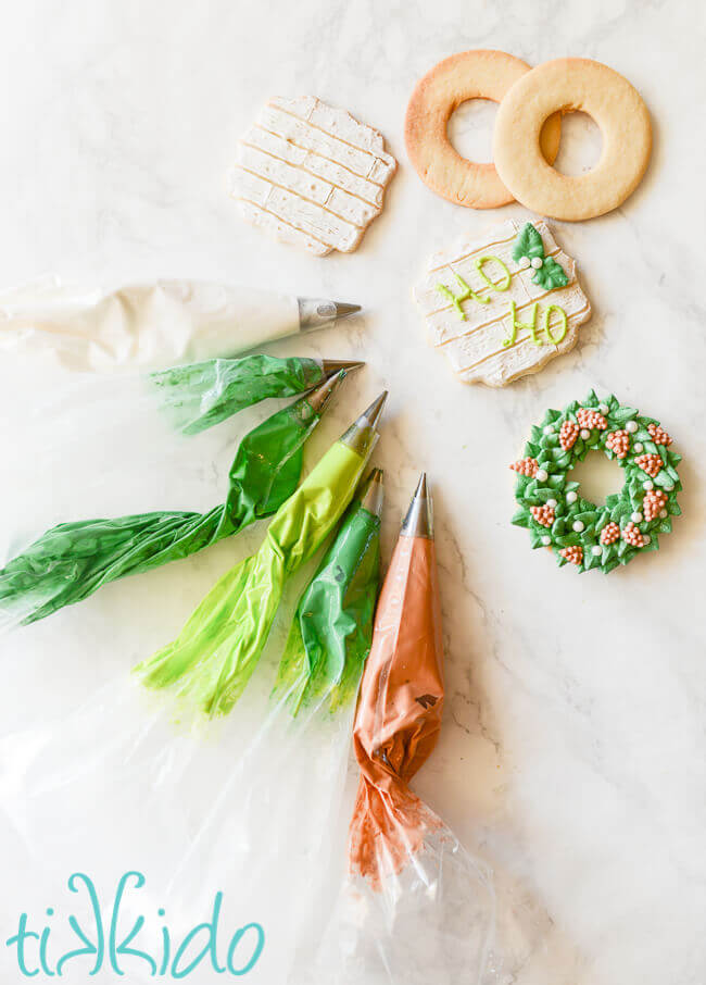 Bags of green and brown royal icing next to decorated and undecorated sugar cookies