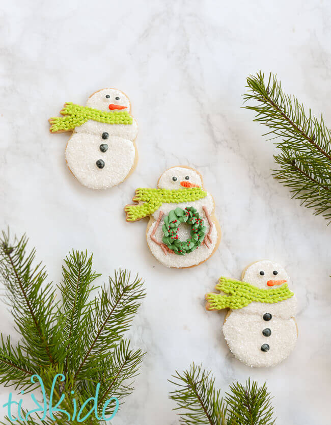 Three snowman sugar cookies on a white marble background, surrounded by fresh Christmas tree branches.