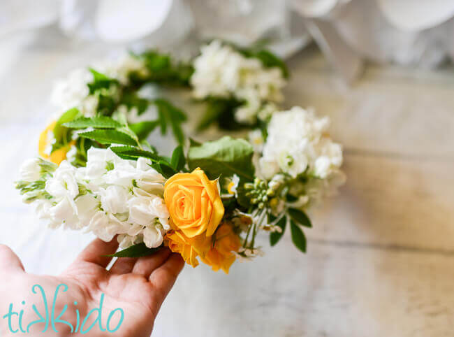 Easy diy fresh flower crown tutorial tikkido hand holding a yellow and white fresh flower crown mightylinksfo