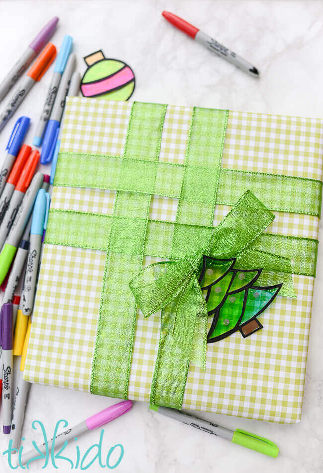 Tree shaped green faux stained glass gift tag on a present wrapped in green gingham and green ribbon. Sharpie markers surrounding present on white marble surface.