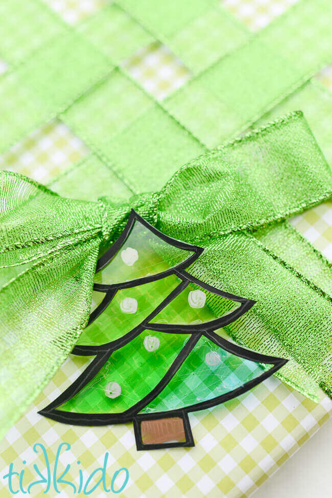Tree shaped green faux stained glass gift tag on a present wrapped in green gingham and green ribbon.
