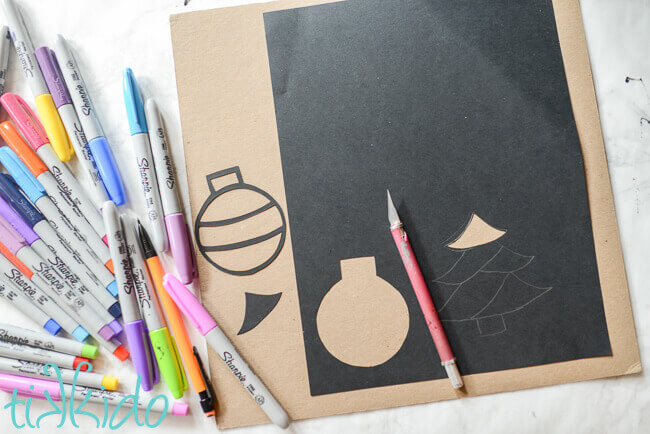Paper ornament and tree shapes being cut out of black card stock with a pink Xacto craft knife, sharpie markers in many colors on the left.