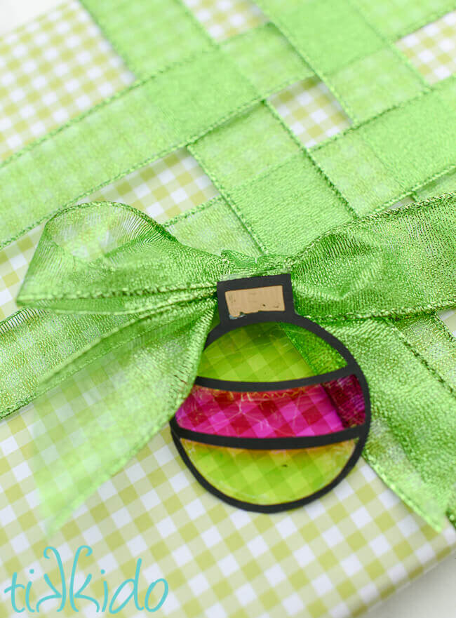 Ornament shaped green and pink faux stained glass gift tag on a present wrapped in green gingham and green ribbon.