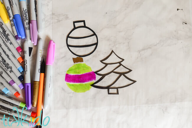 Paper outlines of a tree and ornament shape, green and pink ornament shape colored in on clear plastic film.  Sharpie markers to the left.