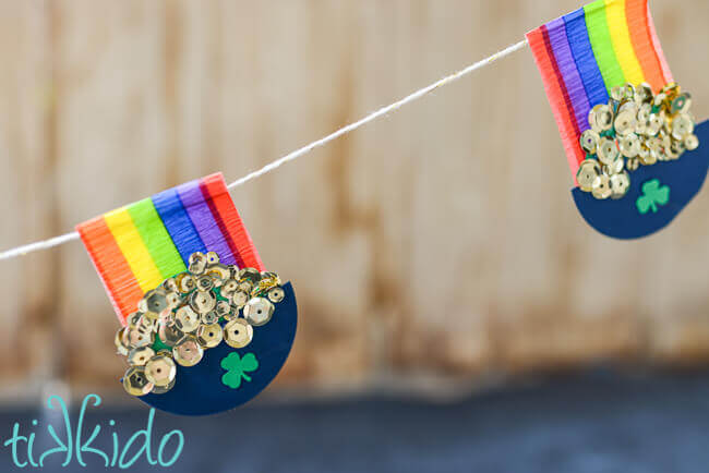 Rainbow and Pot of Gold garland hung in front of a brown wooden backdrop.