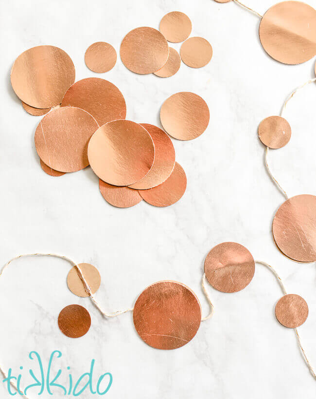 Gold circles of paper in various sizes, scattered on a white marble surface and glued to white and gold baker's twine.