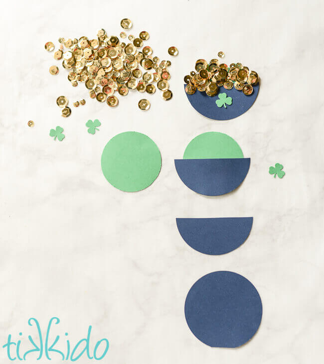 Process of assembling round circles of cardstock together and enhancing with gold sequins to create pots of gold.