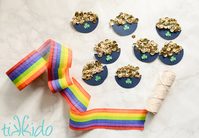 Pot of gold decorations, string, and rainbow crepe paper on white marble background