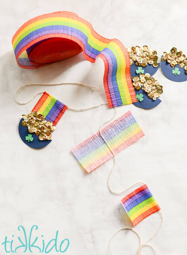 Progressive steps of assembling rainbow crepe paper and paper pots of gold on a St. Patrick's Day garland.