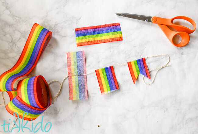 Rainbow crepe paper cut and assembled on string to make rainbow flag bunting.