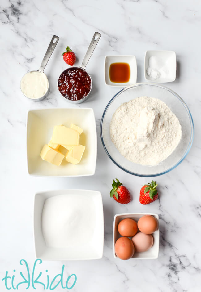 Ingredients for strawberry bread recipe on a white marble surface.