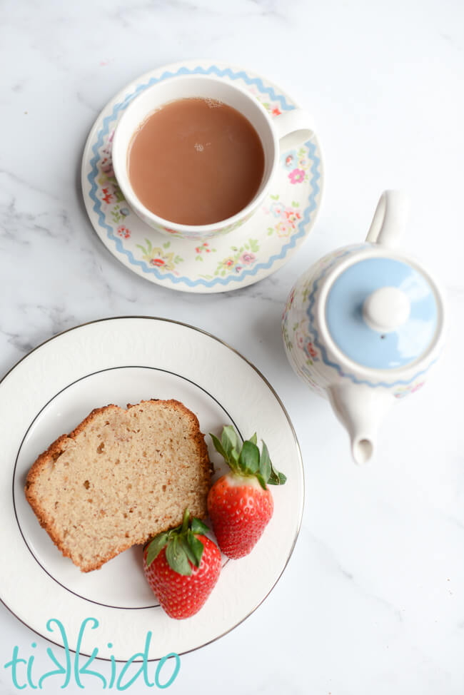 Slice of strawberry bread and two fresh strawberries on a white plate, next to a small teapot and cup of tea.