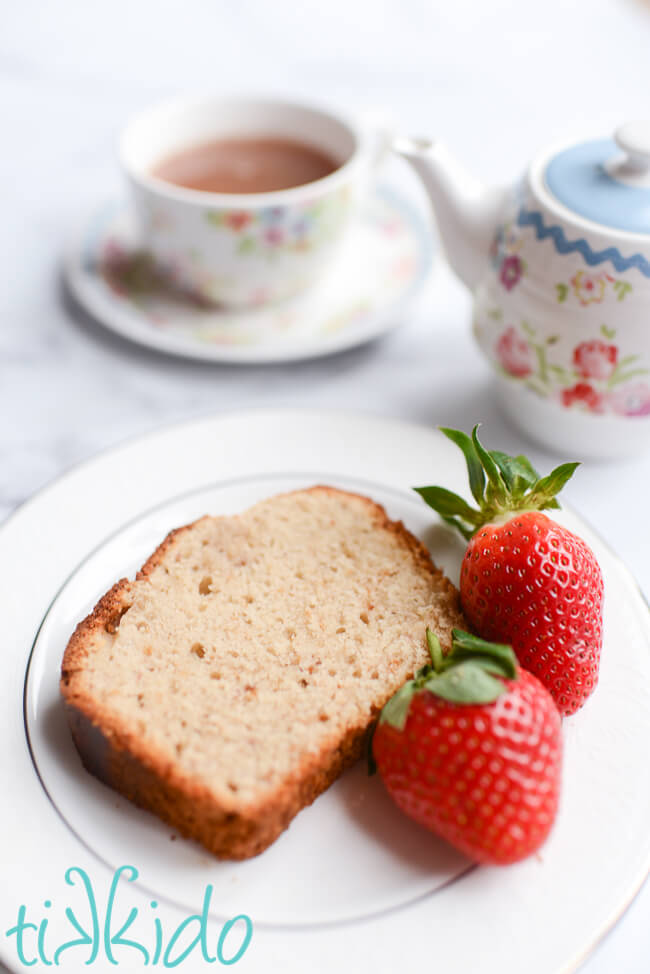 Slice of strawberry bread on a plate with two fresh strawberries, next to a tea pot and cup of tea.