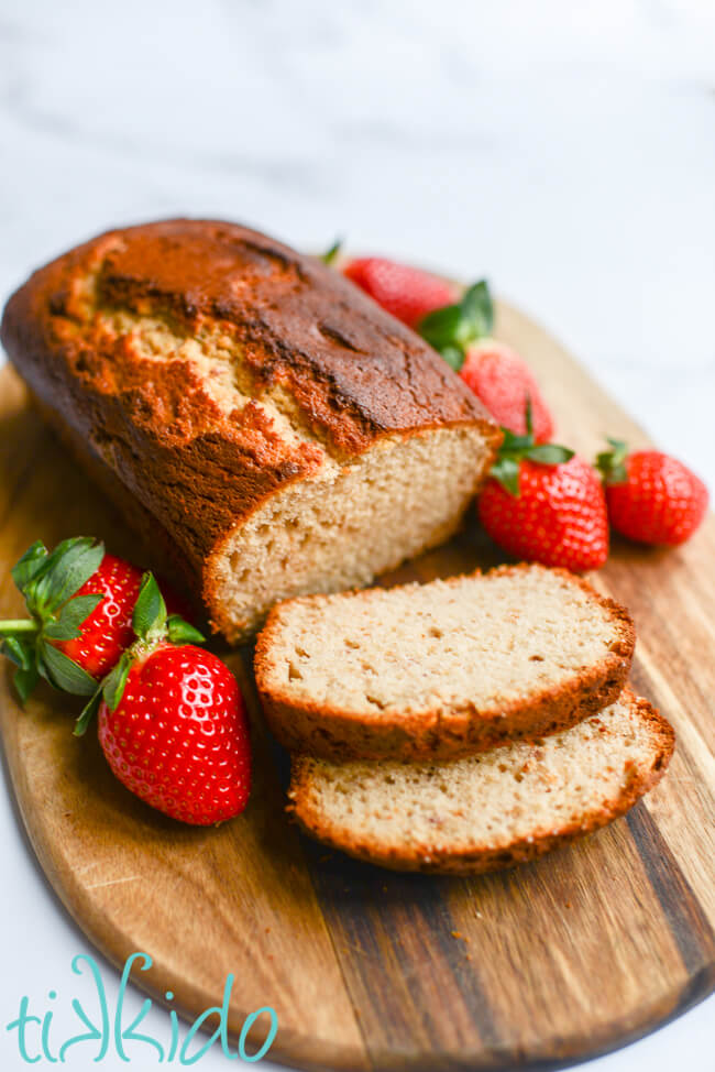 Loaf of strawberry bread with two slices cut, on a wooding cutting board, surrounded by fresh strawberries.