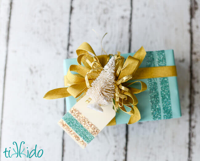 Christmas present wrapped in aqua and gold, topped with a bottle brush tree and a DIY Gift Tag