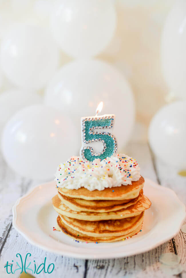 Stack of birthday cake pancakes with whipped cream, sprinkles, and a number 5 candle on top.