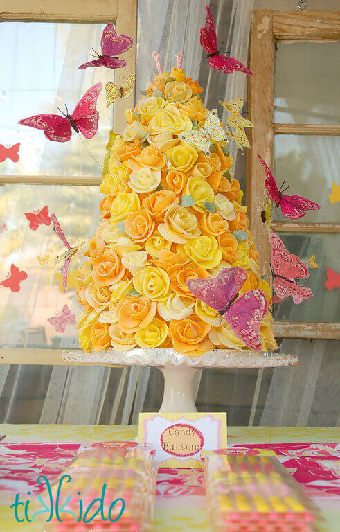 Homemade pink and yellow candy buttons in front of a pink and yellow butterfly rose tower cake.