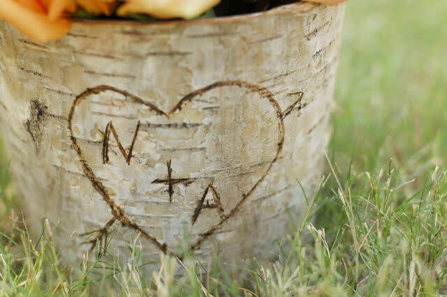 Birch bark covered zinc floral container with the letters N + A in a heart carved into the bark.