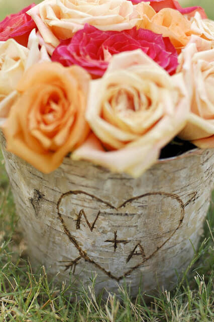 Birch bark covered zinc floral container filled with orange roses with the letters N + A in a heart carved into the bark.