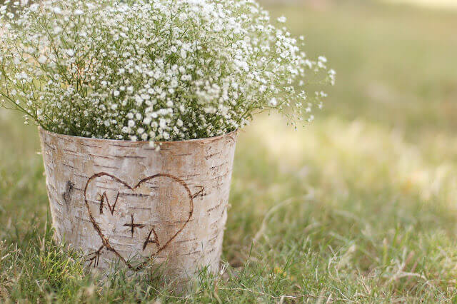 Birch bark covered zinc floral container full of Baby's Breath flowers with the letters N + A in a heart carved into the bark.