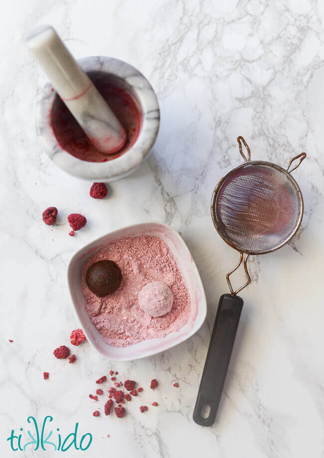 Mortar and pestle, fine mesh strainer, and bowl with raspberry powdered sugar and two truffles being rolled in the sugar.