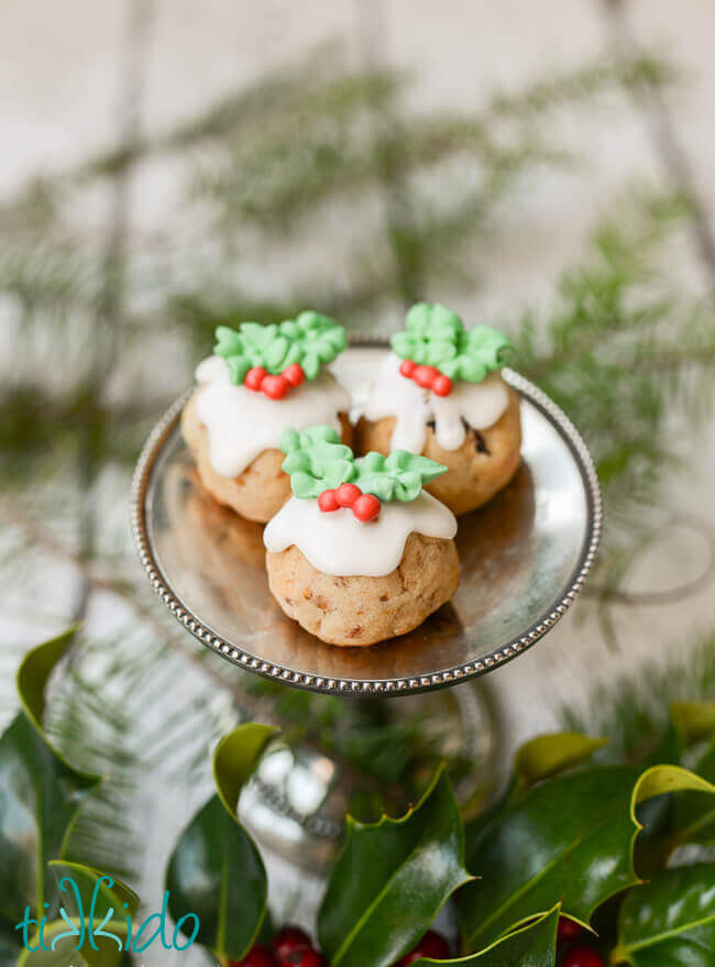 Three Figgy Pudding Cookies on a small silver stand, surrounded by fresh holly and evergreen branches.