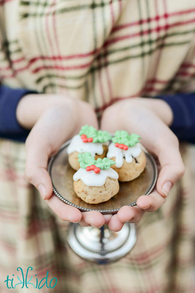 Three Figgy Pudding Cookies on a small silver tray, held in a woman's hands.