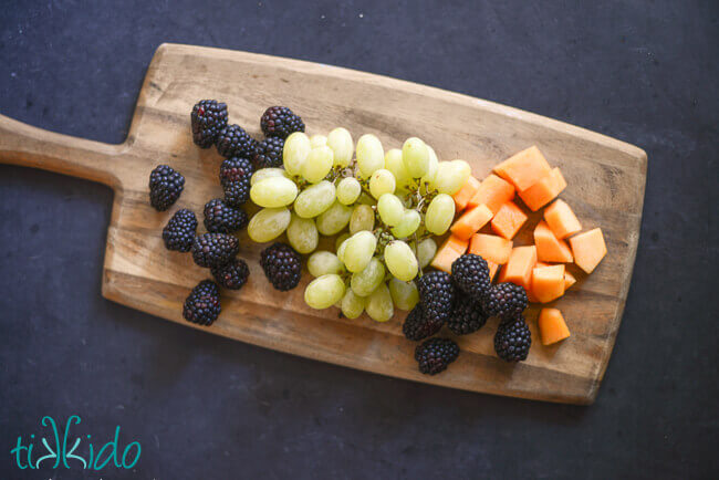 Blackberries, green grapes, and cantaloupe melon on a wooden cutting board.