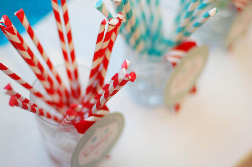 Homemade hot chocolate flavor add ins packaged in striped paper straws.