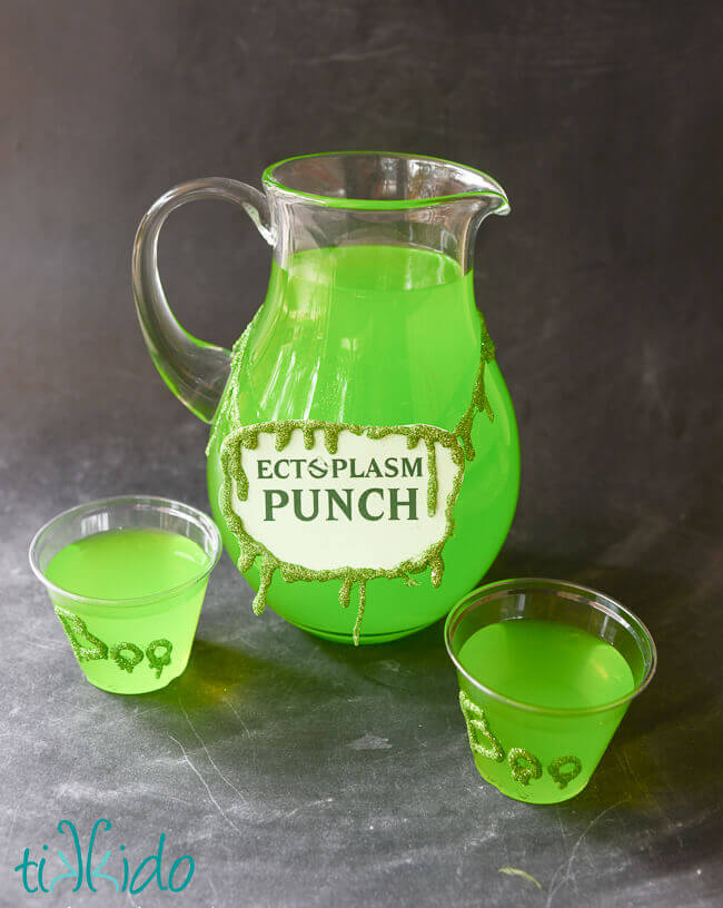 Glitter slime garland decorating a glass pitcher filled with green Ectoplasm Punch.