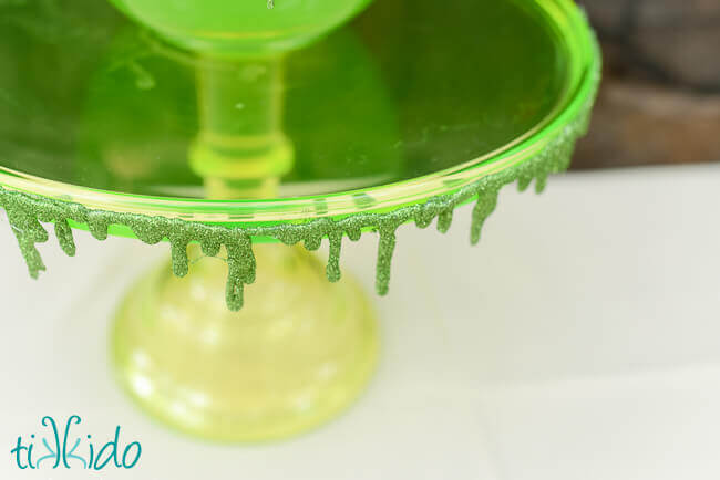 Glitter slime garland decorating a green vaseline glass cake plate.