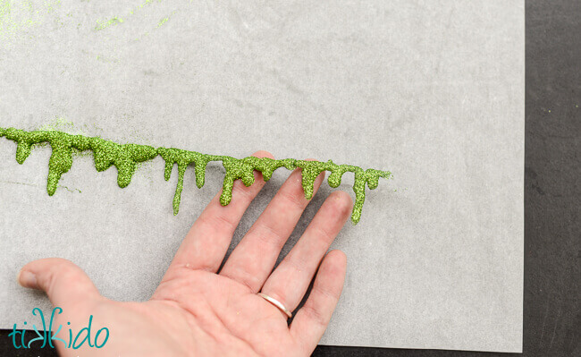 Glitter slime garland being pulled off parchment paper.